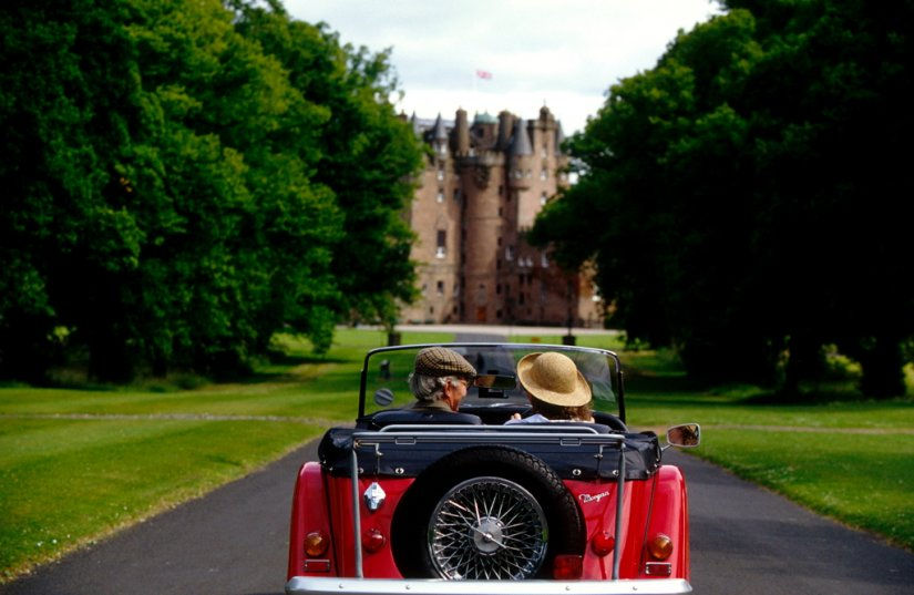 Couple senior en voiture de collection au château de Glamis en Ecosse