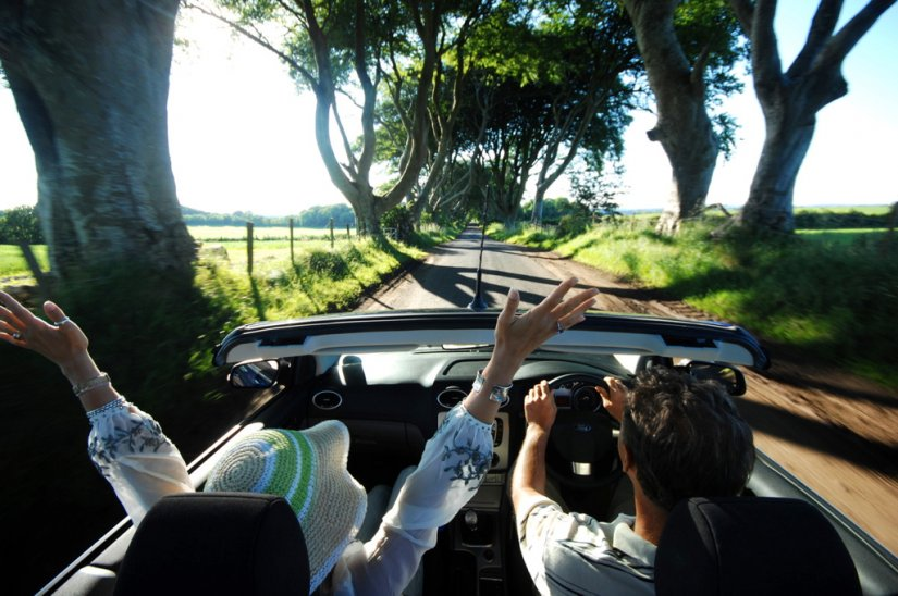 Couple en voiture à Dark Hedges, Paysage de Game of Thrones, Antrim, Irlande du Nord